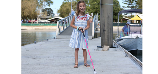 Kaylah standing with her cane
