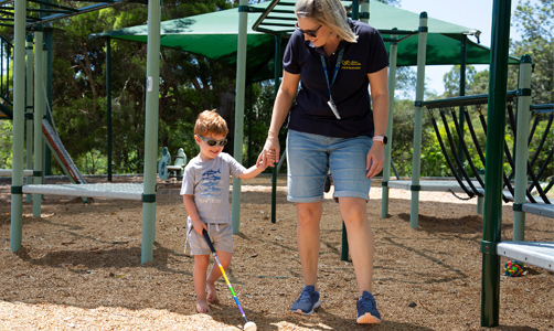 Hugo uses his colourful white cane at the playground and is holding hands with Cathryn