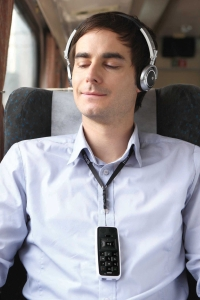 man on train with headphones on listening to audio books from his BookSense DAISY player that is hanging from his neck