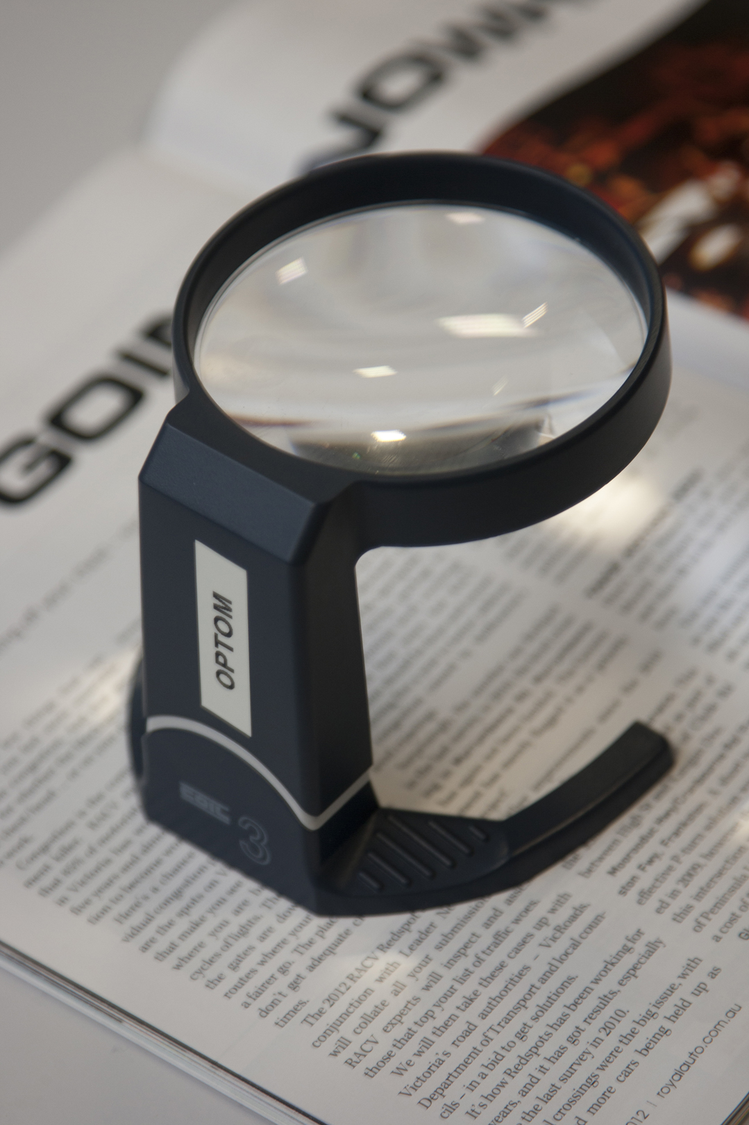Non illuminated stand magnifier on a magazine