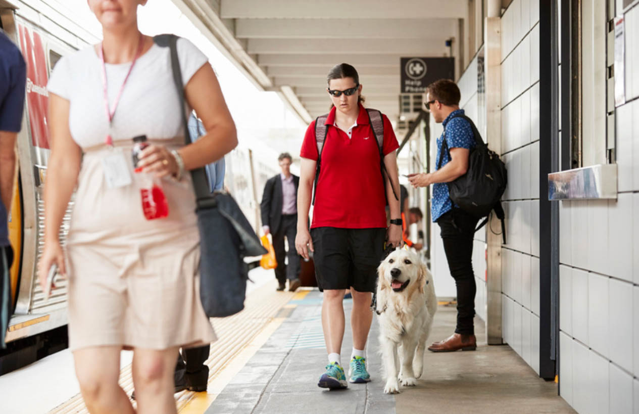 A student walking with her seeing eye dog at a train station